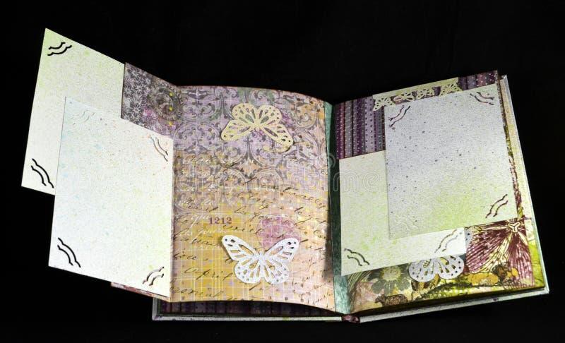 Versteckte Seite auf einer dritten Verbreitung eines kleinen handgemachten photoalbum stockbild