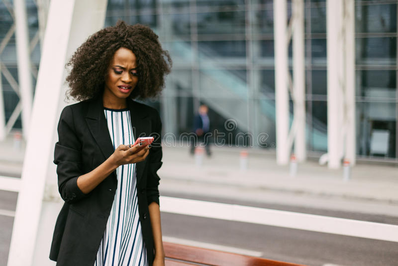 Verstoor Afro-Amerikaanse vrouw bekijkt de mobiele telefoon De gelukkige jonge zakken van de meisjesholding op een witte achtergr stock fotografie