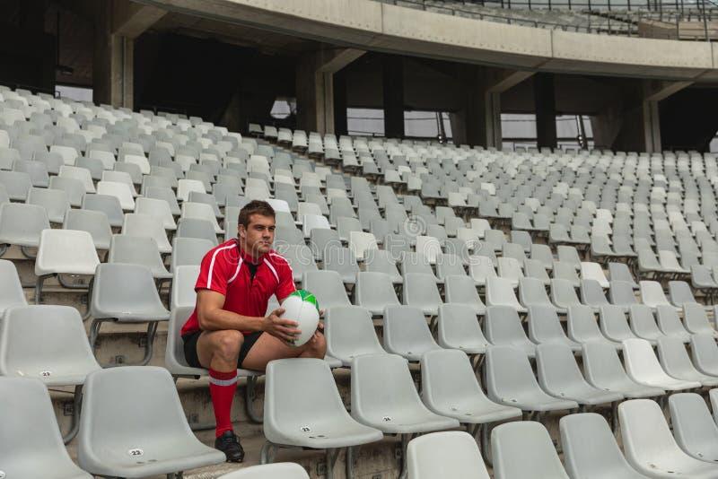 Verstoor de Kaukasische mannelijke zitting van de rugbyspeler met rugbybal in stadion royalty-vrije stock afbeelding