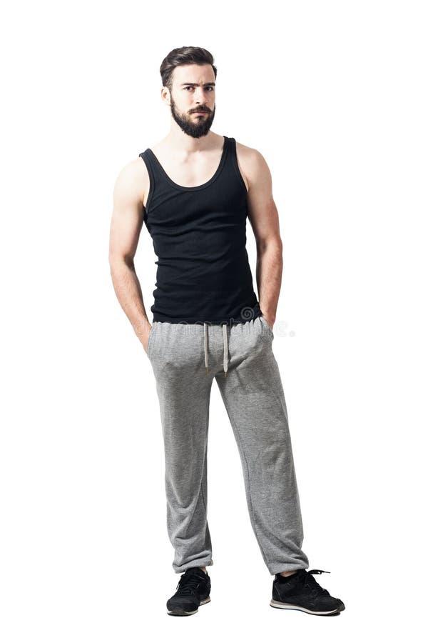 Verstoor gebaarde atleet in mouwloos onderhemd en jogger broek bekijkend camera royalty-vrije stock foto