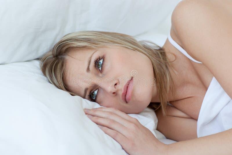 Verstoor het jonge vrouw liggen op haar bed stock fotografie