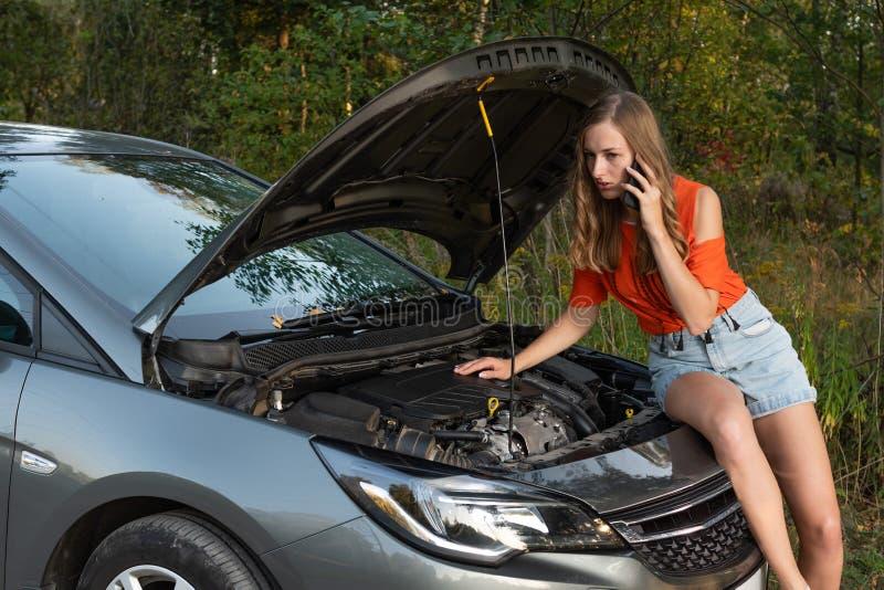Verstoor jonge vrouw met de gebroken auto van de celtelefoon dichtbij - Beeld royalty-vrije stock fotografie