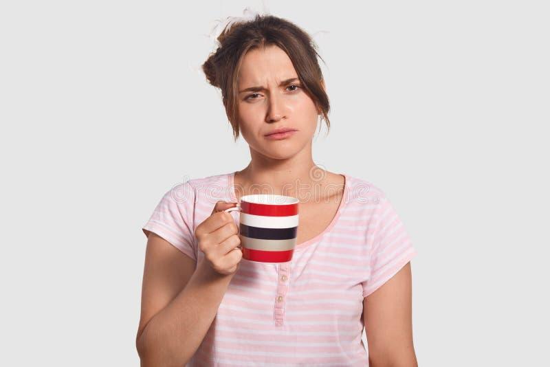 Verstoor slaperige mooie jonge vrouw houdt moedig kop van koffie, drank verfrissende drank om vroeg in ochtend te voelen, gekleed royalty-vrije stock foto's