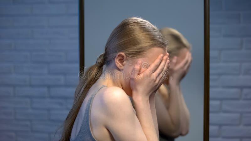 Verstoor tiener vrouwelijk sluitend gezicht met palmen, ongelukkig met huidproblemen, acne stock fotografie