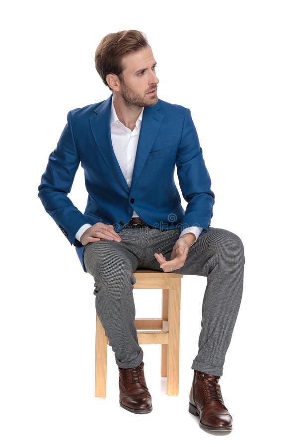 Verstoor toevallige mens zitting en het leunen op zijn been royalty-vrije stock fotografie