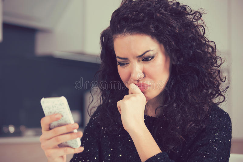 Verstoor verwarde jonge vrouw die mobiel de tekstbericht van de telefoonlezing bekijken royalty-vrije stock fotografie
