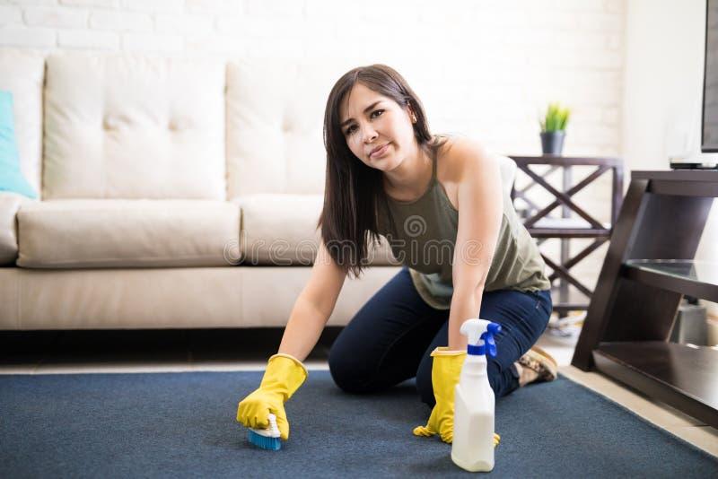 Verstoord en vermoeid vrouwen schoonmakend tapijt thuis royalty-vrije stock fotografie