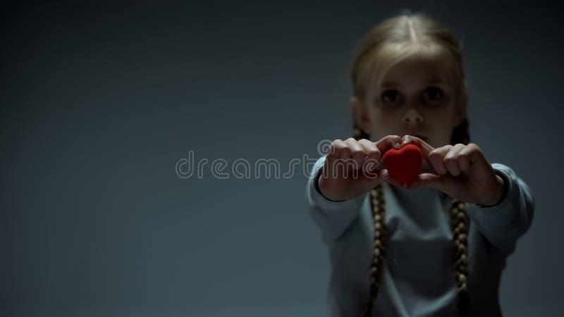 Verstoord meisje die hartcijfer in camera, liefdadigheidsconcept, sociale zekerheid tonen stock fotografie
