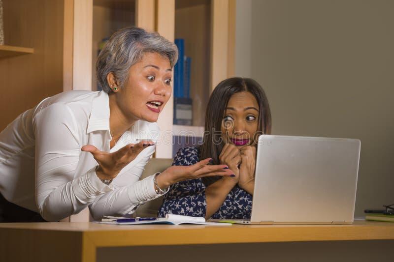 Verstoorde bedrijfsvrouw die en op werknemersmeisje boos zeuren berispen voor computerfout in bureau chef- of belangrijkst gezag  royalty-vrije stock afbeeldingen