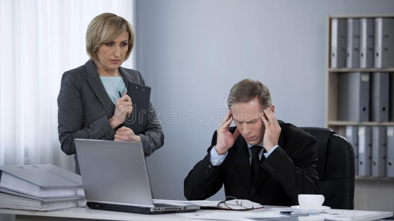 Verstoorde beklemtoonde bedrijfsmens die aan hoofdpijn lijden, die secretaresse samenkomen stock afbeeldingen