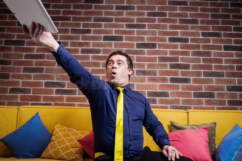 Verstoorde beklemtoonde, boze bedrijfsmens die zijn digitale tablet, U werpen royalty-vrije stock foto's