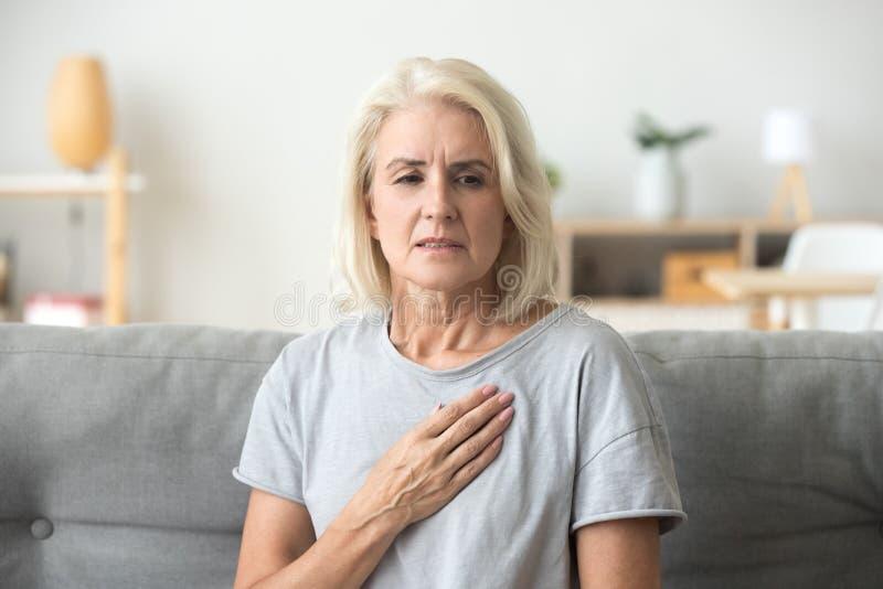 Verstoorde beklemtoonde rijpe oudere vrouw die hartzeer wat betreft che voelen stock afbeeldingen
