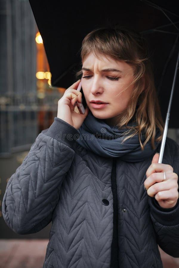 Verstoorde dame die zich op straat met zwarte paraplu bevinden en op haar cellphone spreken stock afbeelding