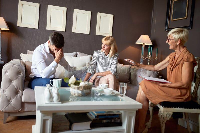 Verstoorde echtgenoot met vrouw bij psycholoog royalty-vrije stock afbeeldingen
