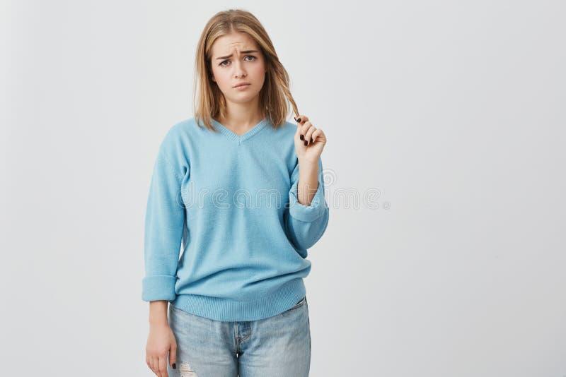 Verstoorde en niet bevallene jonge vrouw met ovaal gezicht, donkere ogen en eerlijk recht haar die blauwe toevallige sweater drag royalty-vrije stock afbeeldingen