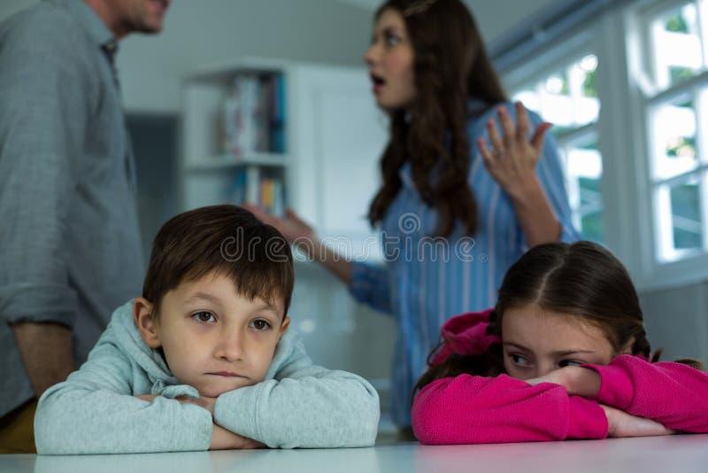 Verstoorde kinderen die terwijl paar die met elkaar debatteren zitten stock afbeeldingen