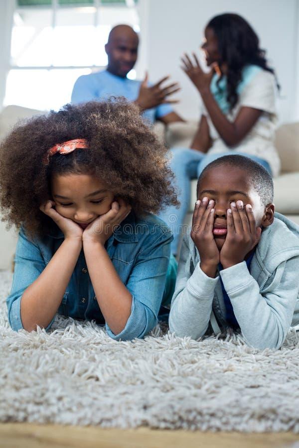 Verstoorde kinderen met ouders die met elkaar debatteren stock foto's