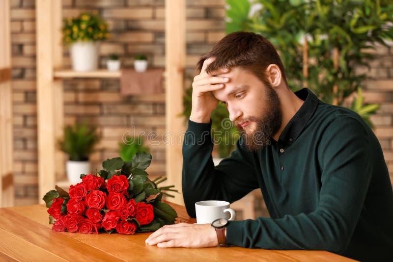 Verstoorde mens die op zijn meisje in koffie wachten stock foto