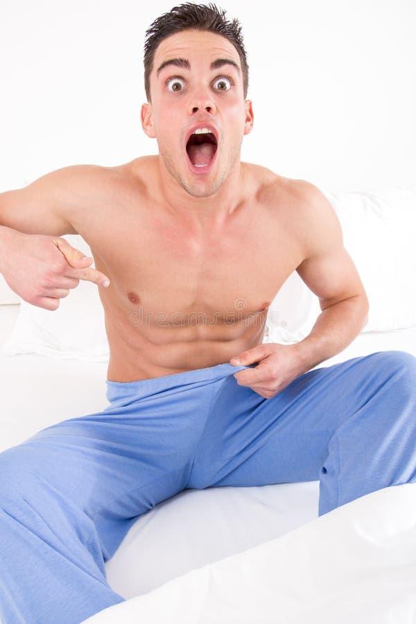 Verstoorde mens op bed in pyjama's die problemen met impotentie hebben stock afbeelding
