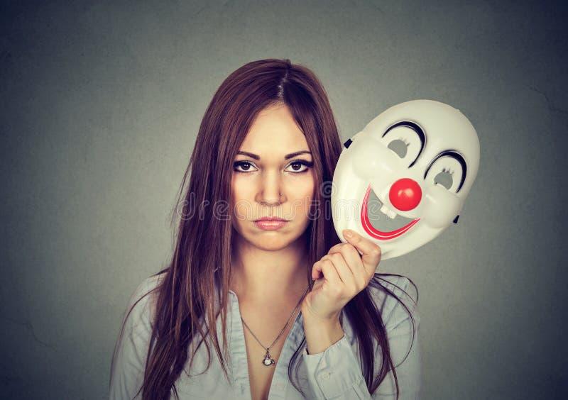 Verstoorde ongerust gemaakte vrouw met droevige uitdrukking die clownmasker van start gaan royalty-vrije stock fotografie
