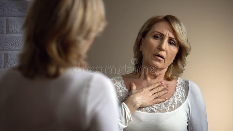 Verstoorde in spiegel kijken en nauwelijks vrouw die, gezondheidsproblemen, hartpijn ademen stock foto's