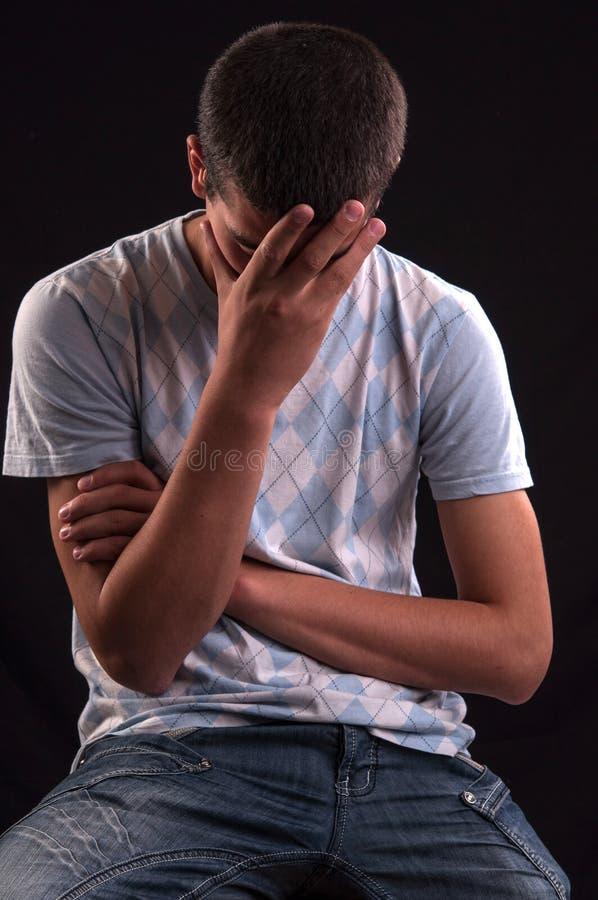 Verstoorde tiener met hand op hoofd stock fotografie