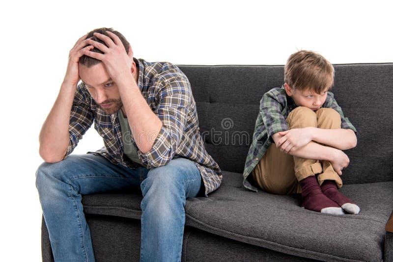 Verstoorde vader en zoonszitting op bank na ruzie royalty-vrije stock afbeelding