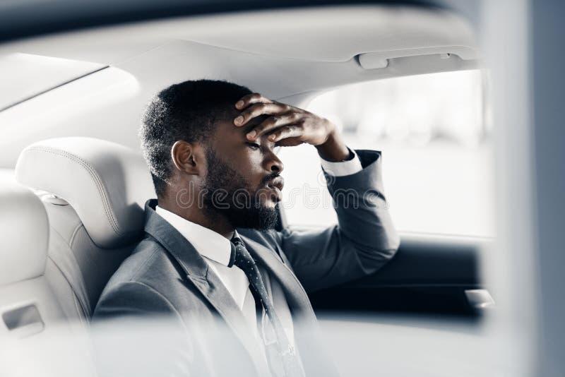 Verstoorde vermoeide zakenmanzitting in auto, die over verbreken denken stock afbeeldingen
