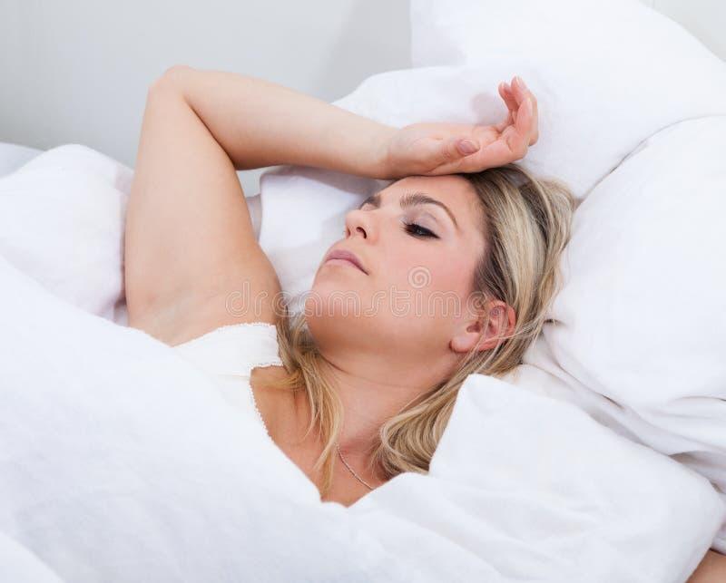 Verstoorde vrouw die op bed liggen stock fotografie