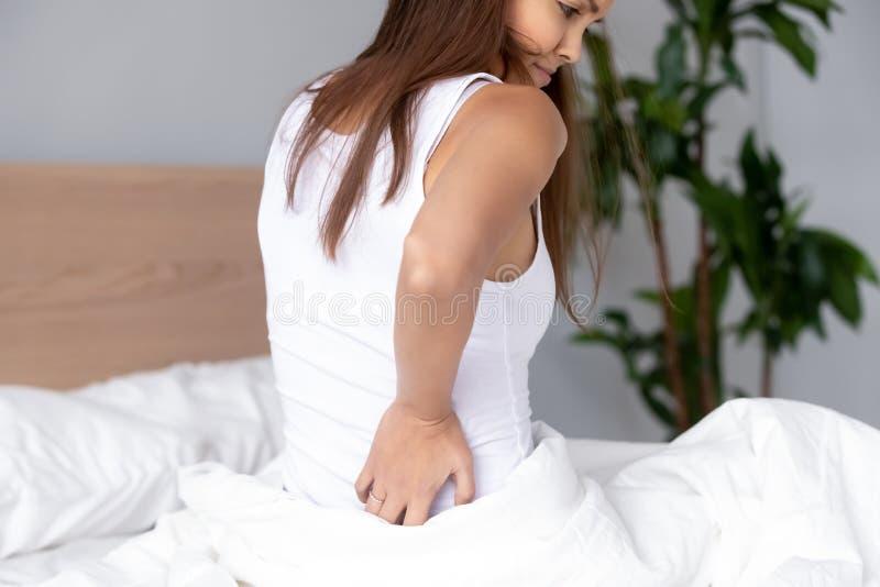 Verstoorde vrouwenzitting in bed, die stijve achterspieren na ontwaken wrijven stock afbeeldingen