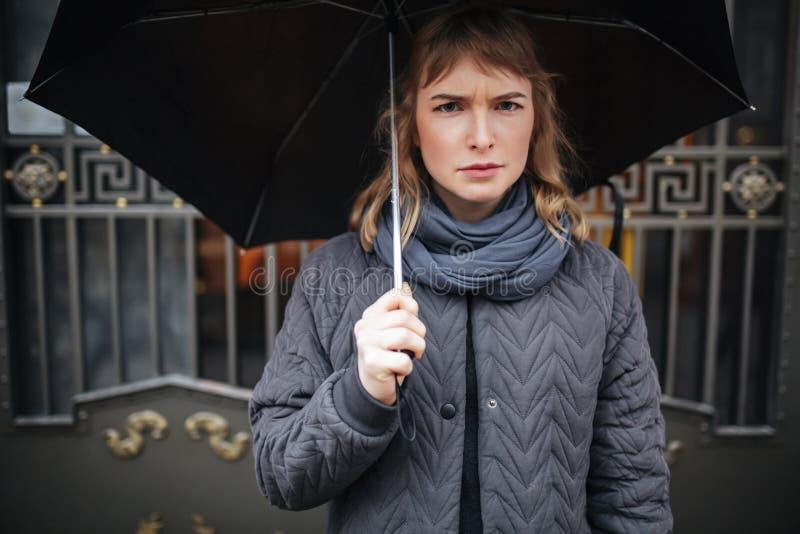 Verstoorde zich op straat met zwarte paraplu bevinden en droevig dame die in camera kijken stock foto's