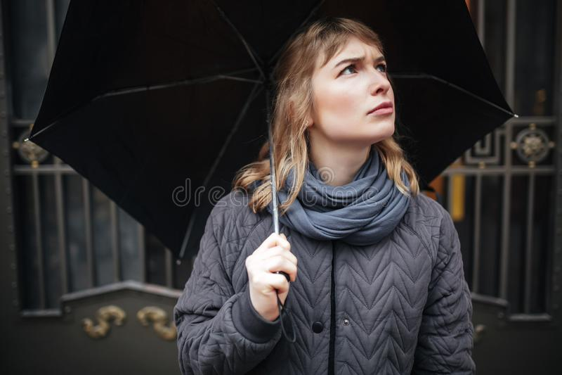 Verstoorde zich op straat met zwarte paraplu bevinden en droevig dame die omhoog kijken stock afbeelding