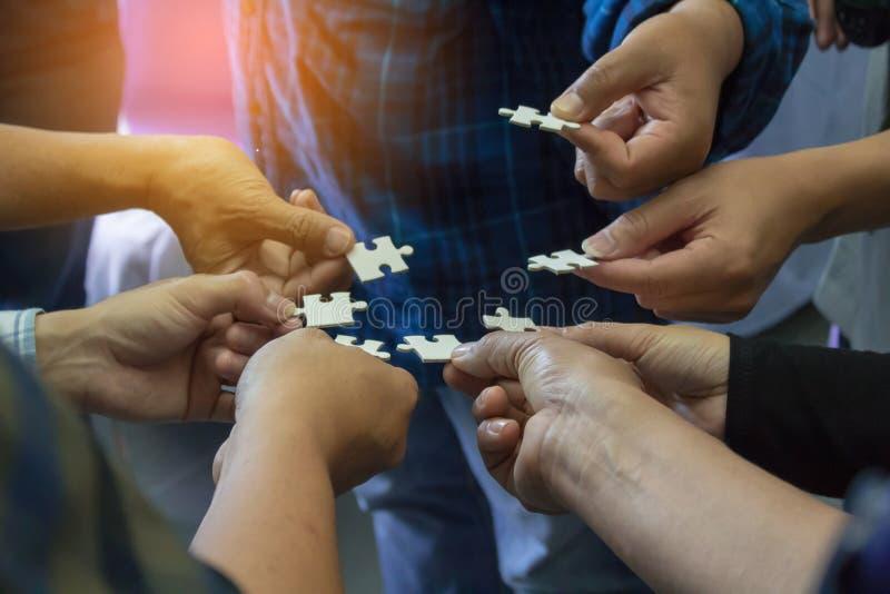 Versuchen, das Puzzlespiel durch Puzzlespiele von Geschäftsmännern zu lösen lizenzfreies stockfoto