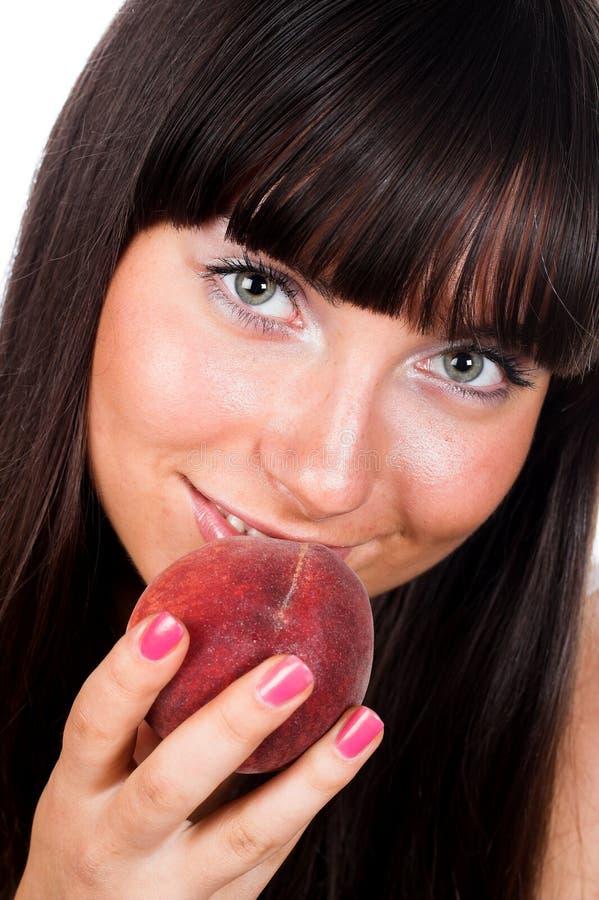 Versuchen, in einen Pfirsich zu beißen lizenzfreies stockfoto