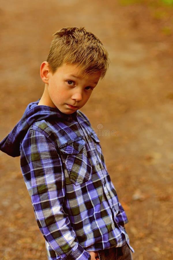 Versuchen, meinen besten kleinen Jungen mit entzückendem Blick zu schauen Entspannte Kleidung der Abnutzung des kleinen Jungen im lizenzfreie stockfotografie