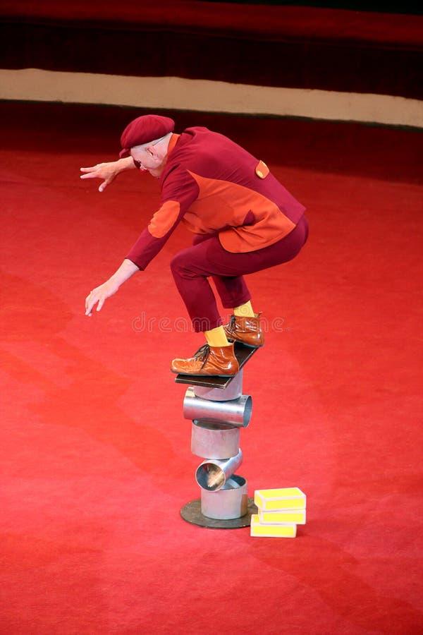 Versuchender Stand des lustigen Clowns auf Gleichgewicht auf Spulen Fröhlicher Clown, der Zirkustrickbalanceakt auf Zylindern dur lizenzfreie stockfotos