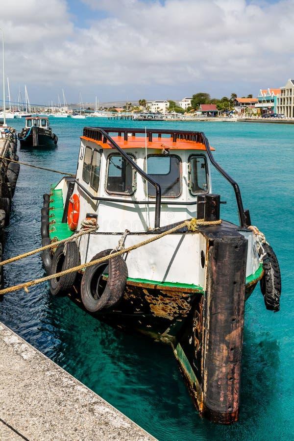 Vert blanc et bateau de pêche rouge attachés au dock images stock