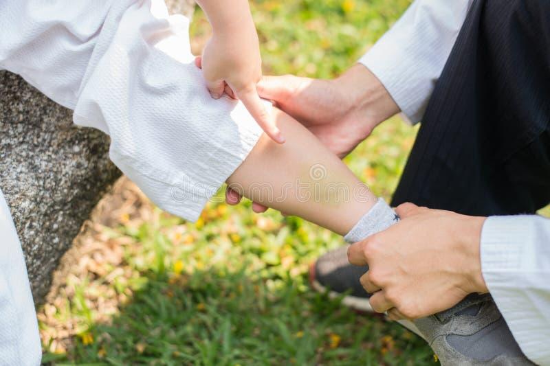 Vert clair sur la jambe des enfants meurtrissez et mal, il indiquant le doigt la lésion et la jambe de contact de père pour l'aid image libre de droits