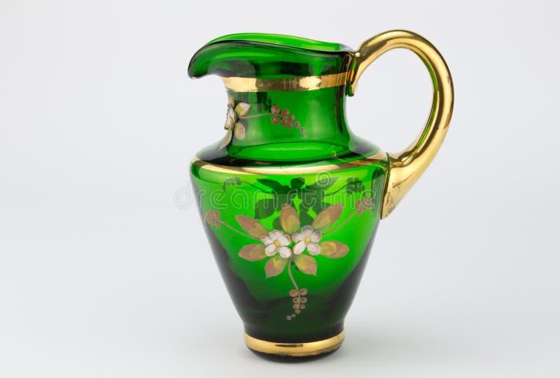 Vert de vintage et cruche de lait soufflée par main en verre d'or sur le whi photos libres de droits
