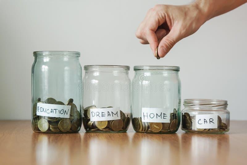 Verteilung des Bargeldeinsparungenskonzeptes Hand setzt Münzen zu den Glasgeldkästen stockfoto