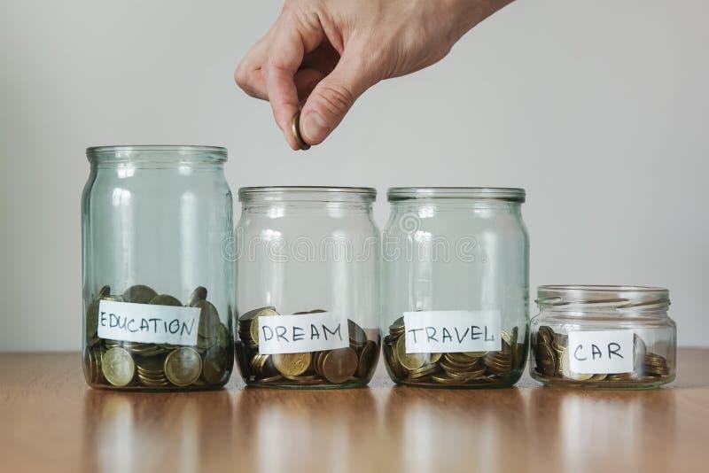 Verteilung des Bargeldeinsparungenskonzeptes Hand setzt Münzen zu den Glasgeldkästen lizenzfreies stockfoto