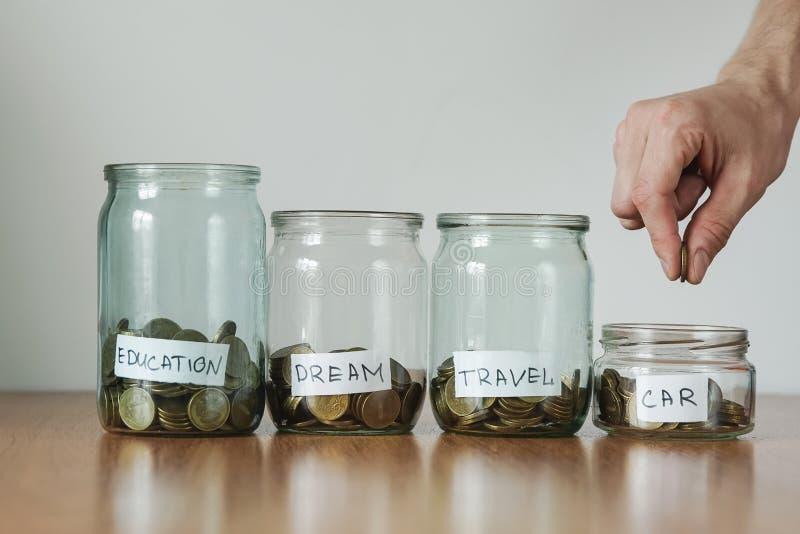 Verteilung des Bargeldeinsparungenskonzeptes Hand setzt Münzen zu den Glasgeldkästen lizenzfreies stockbild