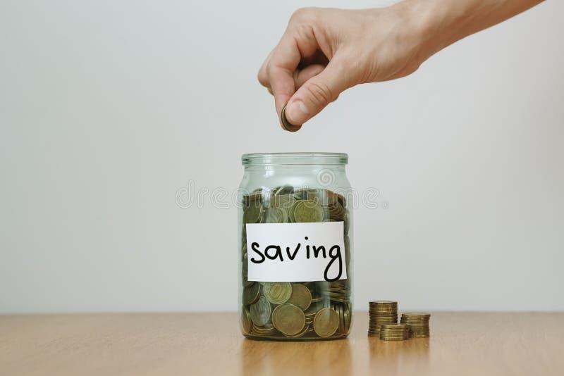 Verteilung des Bargeldeinsparungenskonzeptes Hand setzt Münzen zu den Glasgeldkästen mit Aufschrift ` Einsparung ` stockfotos