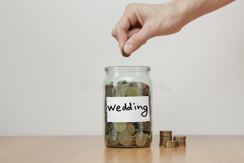 Verteilung des Bargeldeinsparungenskonzeptes Hand setzt Münzen zu den Glasgeldkästen mit Aufschrift ` Hochzeit ` lizenzfreies stockbild