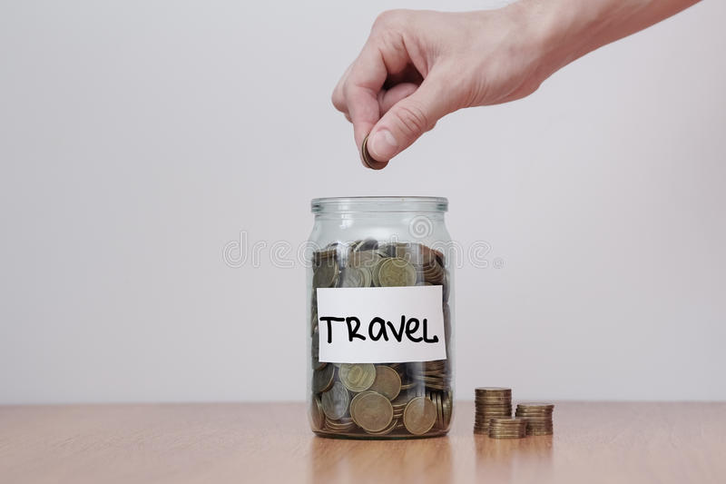 Verteilung des Bargeldeinsparungenskonzeptes Hand setzt Münzen zu den Glasgeldkästen mit Aufschrift ` Reise ` lizenzfreie stockfotografie