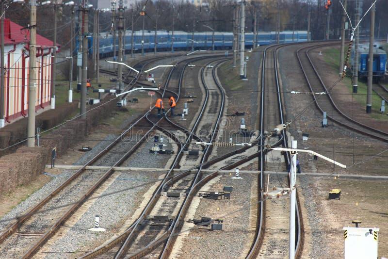 Verteilungsstationseisenbahn Schienen und Lagerschwellen, das Personal des Bahnhofs in der speziellen Kleidung, die den Schaden r stockbilder