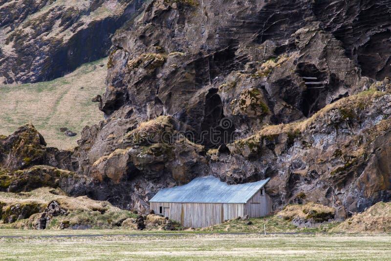 Vertente da exploração agrícola de Drangshlid construída na formação de rocha Drangurinn em Islândia foto de stock