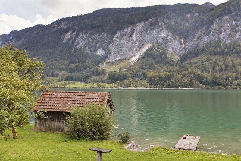 Vertente de madeira velha do pescador na costa do lago da montanha imagens de stock royalty free