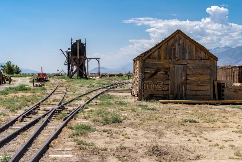Vertentes abandonadas velhas do poço de petróleo e do armazenamento, peça da estrada de ferro anterior das leis em Inyo County Ca fotografia de stock