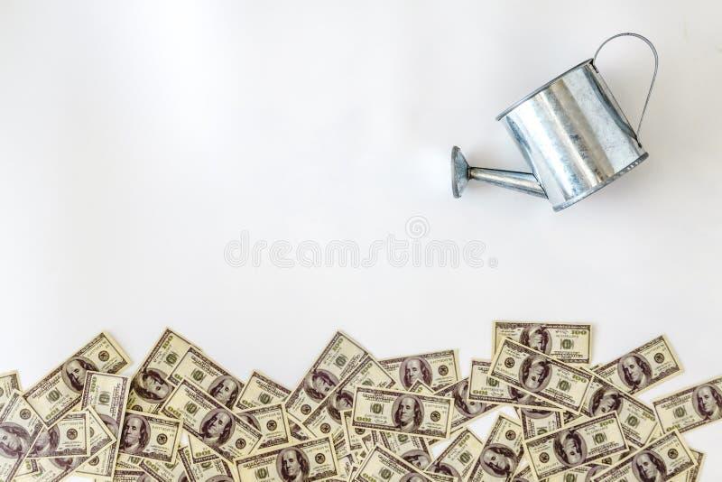 verter-regado de los dólares de los billetes de banco de la regadera en un fondo blanco Concepto, inversión, negocio de lanzamien foto de archivo libre de regalías